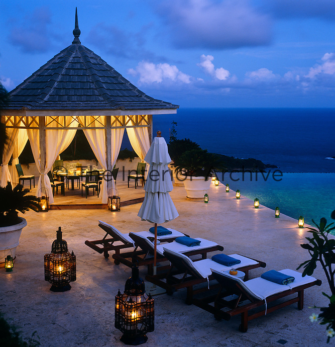 At night the swimming pool terrace twinkles in the candlelight from rows of storm lanterns and the dining gazebo is laid for dinner