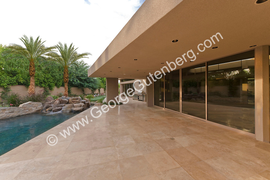 Travertine patio deck is seen next to swimming pool of large estate