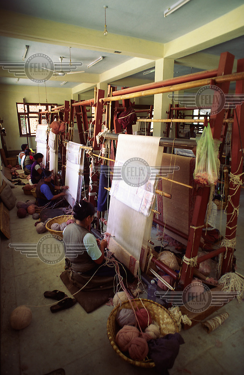 Tibetan refugee women weaving carpets.