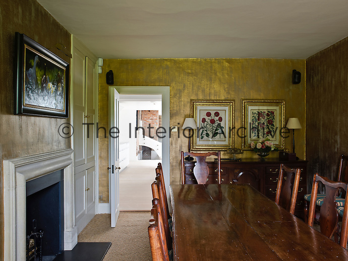 The dining room with its gold wall treatment is unexpectedly traditional