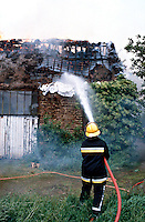Firefighters fighting a barn fire. They are aiming the main jet through the thatched roof in an attempt to stop the fire from spreading...© SHOUT. THIS PICTURE MUST ONLY BE USED TO ILLUSTRATE THE EMERGENCY SERVICES IN A POSITIVE MANNER. CONTACT JOHN CALLAN. Exact date unknown.john@shoutpictures.com.www.shoutpictures.com.