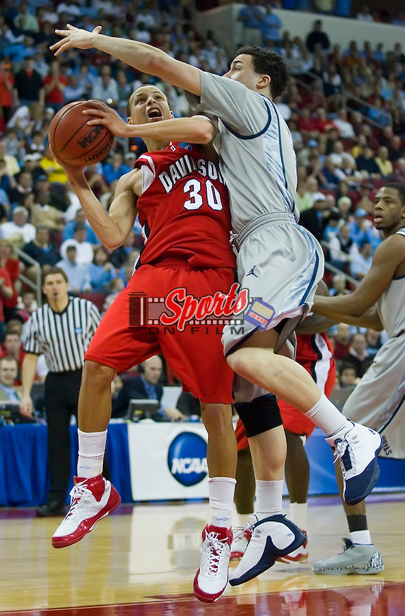 Stephen Curry (30) of the Davidson Wildcats is fouled by Jeremiah Rivers (5) of the Georgetown Hoyas in second round action of the 2008 NCAA Men's Basketball Championship at the RBC Center in Raleigh, NC, Sunday, March 23, 2008.