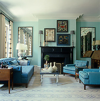 The duck egg blue walls of this tranquil living room are complimented by a seating arrangement upholstered in soft blue; the paintings are by Willem Hussem