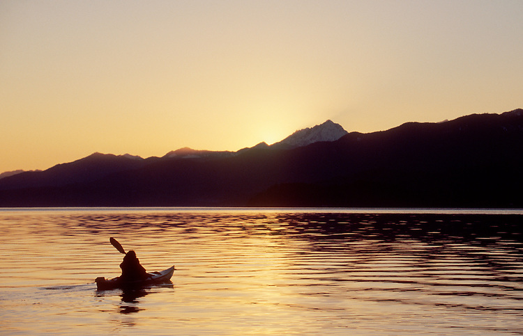 Sea Kayaking, Hood Canal, Woman sea kayaker paddles toward sunset,  Olympic Mountains, Puget Sound, Washington State, Pacific Northwest, USA, .