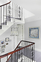 Silver lanterns on long rods hang down the centre of the stairwell to the entrance hall
