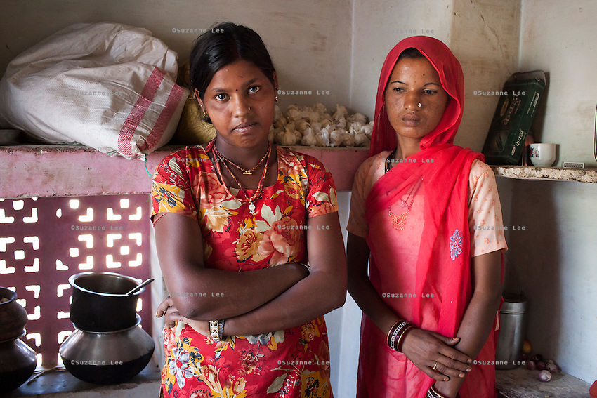 Nitu and Suki (in pink) (not their real names), stand for a portrait in their house in Jhaju village, Bikaner, Rajasthan, India on 4th October 2012. Now 18, Nitu was married off at age 10 to a boy of around the same age, but only went to live with her in-laws when she was 12, after she had finished studying up to class 6. The three sisters, aged 10, 12, and 15 were married off on the same day by their maternal grandfather while their father was hospitalized. She was abused by her young husband and in-laws so her father took her back after hearing that her husband, who works in a brick kiln, was an alcoholic and was doing drugs and crime. She had only spent a few days at her husband's house at that time. Her father (now out of the hospital) has said that she will only be allowed to return to her husband's house if he changes his ways but so far, the negotiations are still underway. Her sister, Suki, now age 20, was married off at age 12 but only went to live with her husband when she was 14. Her husband died three years after she moved in, leaving her with a daughter, now 6, and a son, now 4. She has no parents-in-laws and thus returned to her parents house after being widowed because her brother-in-law, who had become the head of the family after his brother's death, had refused to allow Suki to inherit her deceased husband's fair share of agriculture land. Although Suki's father wants her to remarry, she refuses to, hoping instead to be able to support her family through embroidery and tailoring work. The family also makes hand-loom cotton to subsidize their collective household income. Photo by Suzanne Lee for PLAN UK