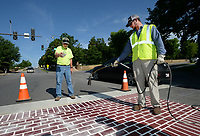 NWA Democrat-Gazette/ANDY SHUPE<br /> James Hoerler (right) uses a propane torch as Brian Polingo, both workers with the city of Fayetteville Transportation Division, sprinkles reflective material as they work together to install crosswalk markings Wednesday, June 5, 2019, at Dickson Street at Arkansas Avenue. Representatives from GEVEKO Markings, which works with the city to supply roadway markings, said work at the intersection should be completed Wednesday.