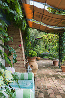 A linen awning extends over the brick-floored terrace overlooking the garden