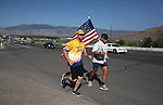 Marine veteran Charlres Padilla, with the flag, runs along Highway 50 in Carson City., on Wednesday, July 3, 2013, as part of a 70-mile run to raise money for wounded veterans. Padilla left Coleville, Ca. on Tuesday evening headed for Virginia City, Nev. Friend Garett Alvey, an Army veteran, joined Padilla for a portion of the run. <br /> Photo by Cathleen Allison