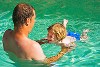 Father teaches his 28 month old daughter to swim.   Model released.