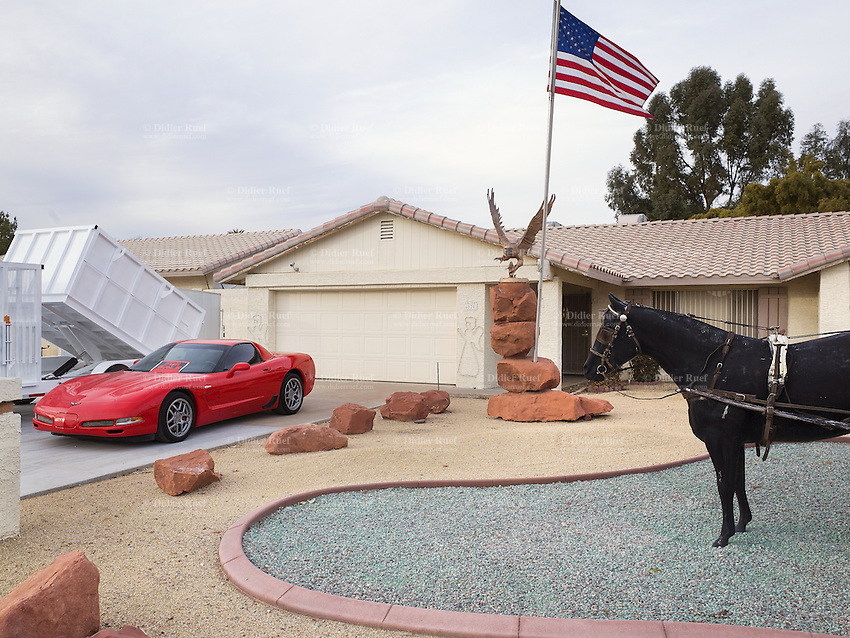 "USA. Arizona state. USA. Arizona state. Scottsdale. A private house with an american flag. A corvette for sale parked in front of the garage's door with two angels on the wall. Metal scuplture of an eagle and a western horse carriage. The american dream. The flag of the United States of America, often referred to as the American flag, is the national flag of the United States. It consists of thirteen equal horizontal stripes of red (top and bottom) alternating with white, with a blue rectangle in the canton (referred to specifically as the ""union"") bearing fifty small, white, five-pointed stars arranged in nine offset horizontal rows of six stars (top and bottom) alternating with rows of five stars. The 50 stars on the flag represent the 50 states of the United States of America. 23.01.16 © 2016 Didier Ruef"
