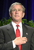 United States President George W. Bush holds his hand over his heart during the presentation of the colors and the playing of the national anthem at the start of the presentation to the 2003 recipients of the Malcolm Baldrige National Quality Award.  A record 7 companies were honored with the national award in quality and preformance excellence.   The Baldrige National Quality Program (BNQP) is a public-private partnership to improve the performance of United States organizations.  It manages the annual award that is named for former United States Secretary of Commerce Malcolm Baldrige.  Secretary Baldrige served under United States President Ronald Reagan.<br /> Credit: Ron Sachs / CNP