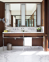 Mirrors above double washbasins give a sense of space in this wood panelled bathroom