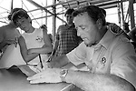 Florida State head coach Bobby Bowden (R) signs his autograph for a young Seminole fan on in the August heat under Doak Campbell Stadium during FSU Picture Day August 11, 1985 (Mark Wallheiser/TallahasseeStock.com)