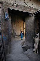 Girl passing an old wooden door leading to the Great Serai. Turquoise Mountain Foundation is working to preserve Afghanistan's traditional crafts and historical buildings. In Kabul, work has started in the historic Murad Khane part of Kabul, and is largely completed in the royal Kart-e-Parwan fort.