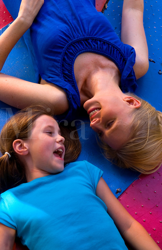 Mother and daughter relaxing together laying on colorful ride andf laughing together outside in park