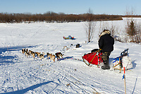 Paul Johnson runs down the road as he leaves Shageluk  on Saturday during Iditarod 2011
