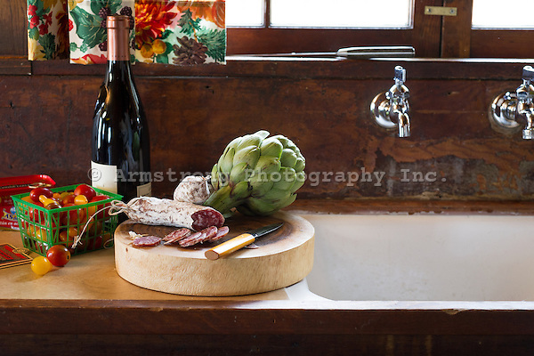 Kitchen countertop and sink in a rustic cabin. On it is a cutting board with sliced salami, an artichoke, and a knife, as well as a bottle of wine and cherry tomatoes.
