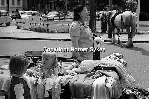 Notting Hill Gate west London 1970s. The top and cheap end of the Portobello Road, Saturday market. Old clothes being sold by mother. Gypsy horse in background. England ..