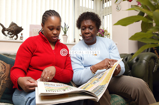 Elderly woman reading newspaper with carer,