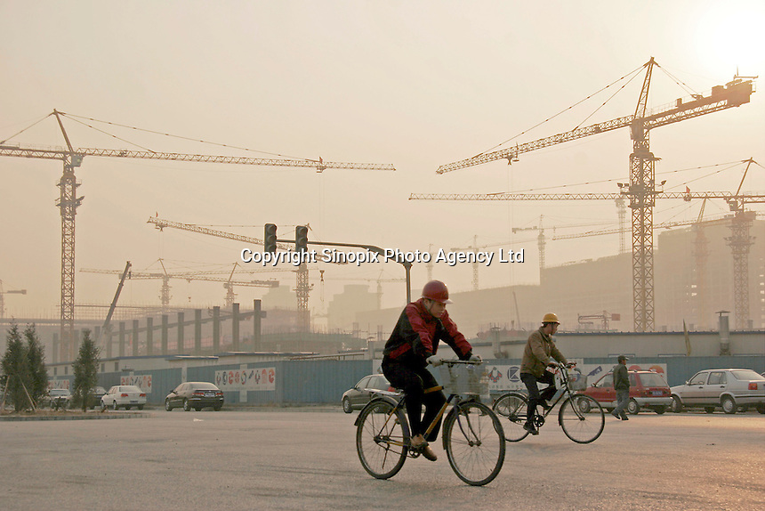 Workers ride their bicycles near the construction site of the Olympic aquatic center in Beijing, China. China's state auditors will extend their search for government corruption next year to the 2008 Beijing Olympics as billions are spent to construct massive Olympic venues..