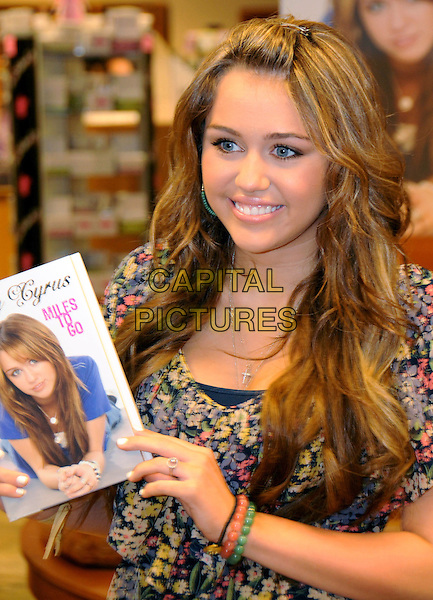 "MILEY CYRUS .Miley Cyrus ""Miles To Go"" Book Signing held at Davis-Kidd Bookstore, Nashville, TN, USA, 9 April 2009..half length floral print top tunic cross necklace holding .CAP/ADM/MS.©Mike Strasinger/Admedia/Capital Pictures"