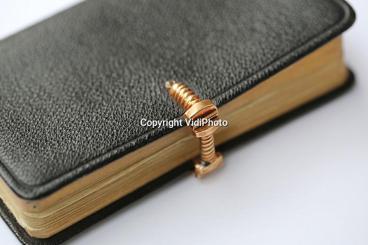 Foto VidiPhoto<br /> <br /> VALBURG - Het gouden slotje op het Bijbeltje van beppe Aaltje de Vries-Bosch. Ooit vormde het goud een onderdeel van het gouden oorijzer van muoike Lysbeth. Het is nu in bezit bij de kleindochter van Aaltje de Vries, Ferdi Janssen-Bakker.