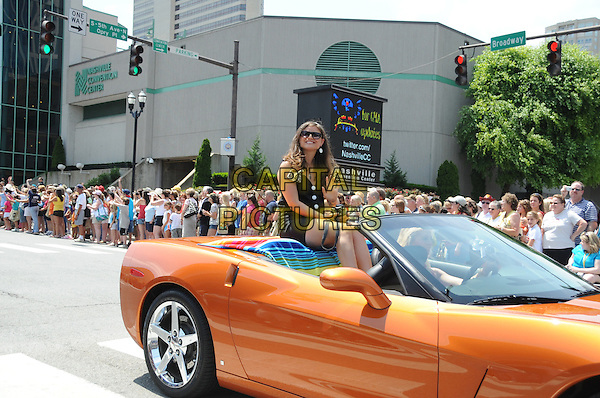 MEGAN MONROE .Rides in the 2009 CMA Music Festival Kick-off Parade, Nashville,TN, USA, .10th June 2009..car country music convertible orange sitting riding half length waving .CAP/ADM/MS.©Mike StrasingerAdmedia/Capital Pictures