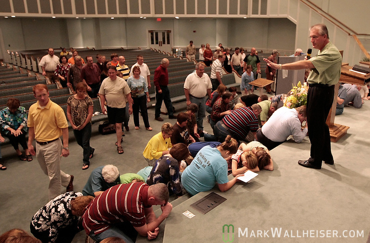 Church members make their way to kneel as Pastor Garry Winstead leads his congregation at the Ino Baptist Church March 11, 2009 in a special prayer for the families affected by the shooting rampage that left 11 people dead March 10, 2009 in the small communities of Samson and Geneva, Alabama. The Ino Baptist Church is near the gunman's home where the shooting spree started with the killing of his mother.   (Mark Wallheiser/TallahasseeStock.com)