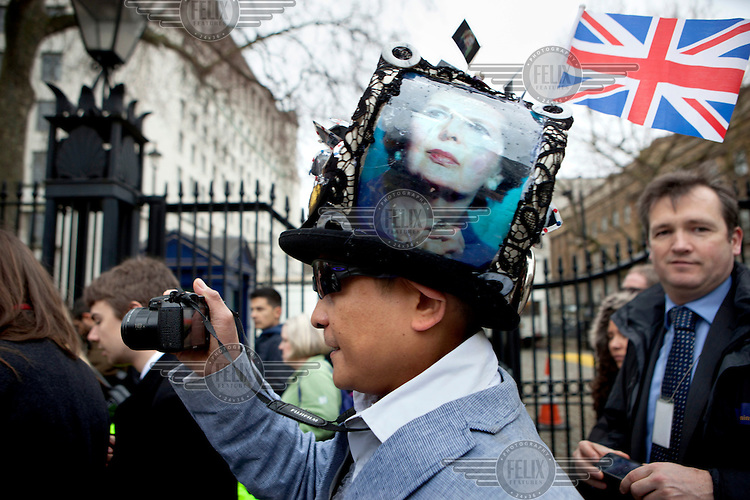 Chito Salarza Grant photographs the funeral of Margret Thatcher as her coffin is taken in a hearse past Downing Street. He wears a hat he created in tribute to the former British Prime Minister who died on 8 April 2013 after suffering a stroke. She was accorded the rare accolade of a ceremonial funeral.