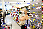 "Theresa Gottardo shops in WalGreens with her dog Snoopy in tow in Sun City, Arizona August 24, 2010. .Theresa, who is originally from northern Italy and moved to Sun City from New York City said she doesn't miss her former homes at all. Sun City ""is quiet, not too expensive,"" she said. ""I enjoy the tranquility. I really enjoy every moment.""..2010 marks the 50th anniversary of the United States' first planned retirement city. When Del Webb created Sun City and it opened in 1960, it was a revolutionary idea for retirees to move away from home and to live extremely active and social lifestyles.."