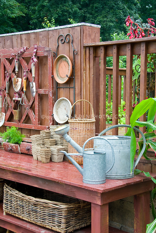 Garden potting bench and containers, galvanized watering cars, baskets, hanging antique tools, pots, asparagus fern growing in old drawer, for charming place outdoors for gardening chores