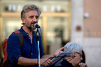 """Ascanio Celestini (Actor).<br /> <br /> Rome, 27/07/2020. Today, hundreds of people, NGO's (ONG) representatives, actors and politicians gathered in Piazza San Silvestro (near the Italian Parliament) to protest (1.) against the dramatic situation in Libya - erupted in a civil war between the GNA (2.) and the forces of General Khalifa Belqasim Haftar - and to protest against the inhumane conditions of migrant people trapped in legal and illegal prisons in Libya. The aim of the demo was to call the Italian Government to stop funding the """"Libyan Coast Guard"""" and to immediately help and free People in Libya throughout """"Humanitarian Corridors"""", and give them the protection they are entitled of by the International Human Rights Conventions. <br /> From the organisers Facebook event page: «[…] we meet to ask the Italian Government and the European States to stop funding the so-called Libyan coast guard, to close and evacuate the detention centres by transferring migrants out of Libya and to promote corridors to help people on the run find protection without endangering their lives. The men, women and children who take the sea from the Libyan coast flee from situations of extreme misery, despotic regimes, tribal persecutions, ethnic conflicts, wars and environmental catastrophes. And in Libya they are subjected to violence, extortion, detention, torture, rape and torture. A few days ago, on July 16, the Chamber of Deputies [Of the Italian Parliament, ndr] for the fourth consecutive year approved the financing of the Italian mission in Libya, which provides financial support for the so-called Libyan coastguard and training and training of its members. […] The mobilization will be accompanied by readings by Ascanio Celestini, Valentina Carnelutti, Fabrizio Gifuni and Sonia Bergamasco […]».<br /> <br /> Footnotes & Links:<br /> 1. https://www.facebook.com/events/2732849460337428/<br /> 2. 07.05.19 Prime Minister of Libya Fayez al-Serraj Met Italian PM Giuseppe Conte at Palazzo"""