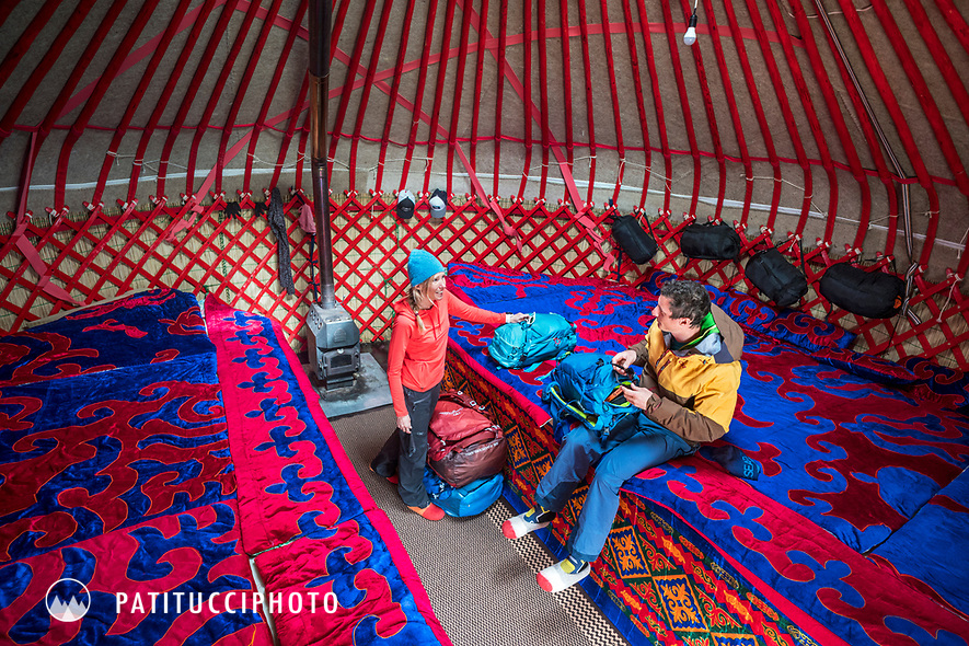 Two skiers unpacking their bags and talking inside a yurt while traveling in Kyrgyzstan