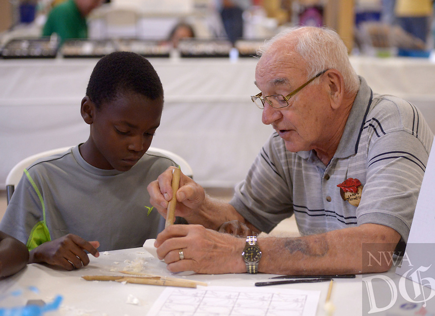 NWA Democrat-Gazette/BEN GOFF @NWABENGOFF<br /> Renando Frost, 9, of Rockford, Ill., learns how to carve using butter knives and bars of soap with guidance from Larry Johnson of the Bella Vista Woodcarvers Club Saturday, July 15, 2017, during the Bella Vista Woodcarvers Club's Artistry in Wood Show at Bella Vista Assembly of God church. Members of the club exhibited and sold their woodwork at the show, which also included door prizes, demonstrations and a people's choice award.