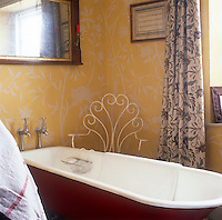 Albion House near Bath, the home of decorative painter Adam Calkin. A yellow bathroom with a floral paint finish on the walls and patterned curtains. A free-standing roll top bath is finished in red.