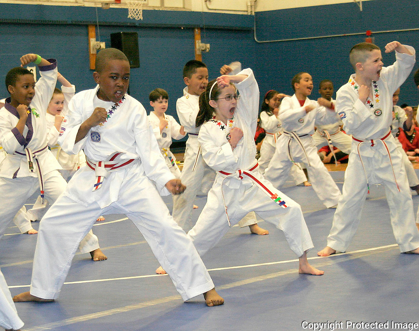 Students give a demonstration with students at the Boston Taekwondo Academy graduation at Randolph High gym Saturday March 31, 2012.(Photo by Gary Wilcox)