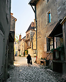 FRANCE, Burgundy, senior woman walking on pathway by buildings, rear view, Noyers