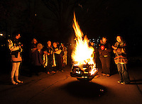 STAFF PHOTO ANDY SHUPE - Residents stand beside a bonfire during a celebration of the winter solstice Sunday, Dec. 21, 2014, at the Unitarian Universalist Fellowship of Fayetteville.