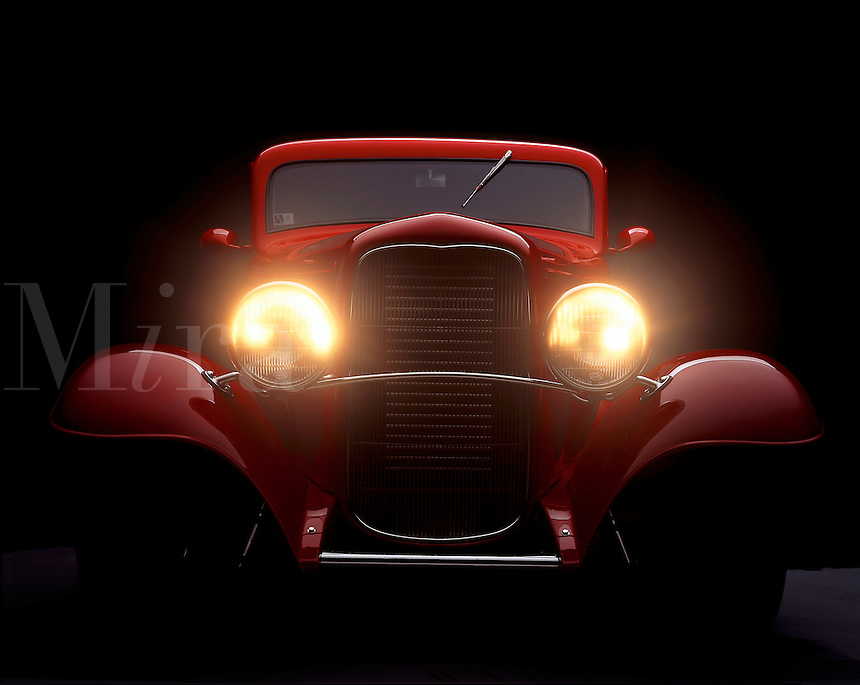 A 1932 Ford with headlights on.