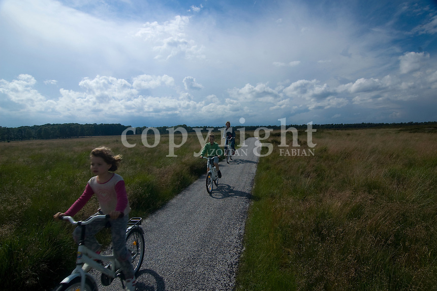 Mother and her children ride a bicycle in Hoge Veluwe, Netherlands