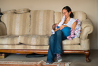 A woman in her early twenties breastfeeding her nine month old baby girl at home while sitting on a sofa in her living room. The baby is playing, touching her mother's face.<br /> <br /> Image from the breastfeeding collection of the &quot;We Do It In Public&quot; documentary photography picture library project: <br />  www.breastfeedinginpublic.co.uk<br /> <br /> <br /> Dorset, England, UK<br /> 08/03/2013<br /> <br /> &copy; Paul Carter / wdiip.co.uk