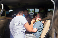 Johnathan Hinojosa of Rogers (from left) administers a nasal swab to Jayden Gonzalez, 4, Friday, June 26, 2020 during a mass covid-19 screening at the Northwest Arkansas Community College in Bentonville. The Arkansas Department of Health hosted a mass screening for anyone at the campus. Their goal was to administer 500 covid-19 tests. NWACC provided the facility and volunteers. UAMS and Mercy Hospital also provided volunteers. Check out nwaonline.com/200627Daily/ for today's photo gallery. <br /> (NWA Democrat-Gazette/Charlie Kaijo)