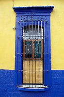 Barred window of restored Spanish colonial house in the city of Oaxaca, Mexico