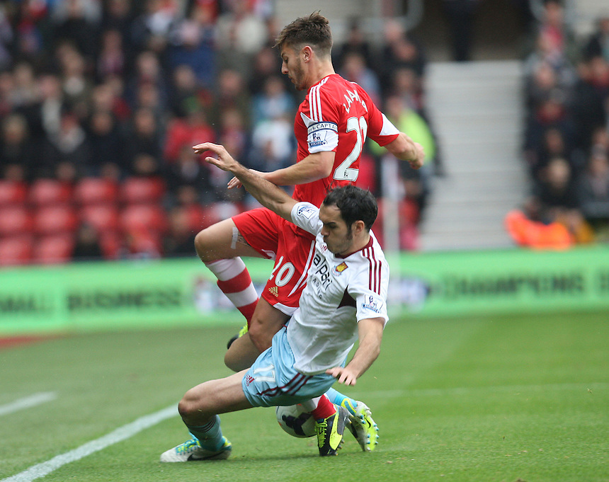 West Ham United's Joey O'Brien tussle with Southampton's Adam Lallana<br /> <br /> Photo by Kieran Galvin/CameraSport<br /> <br /> Football - Barclays Premiership - Southampton v West Ham United - Sunday 15th September 2013 -  St Mary's Stadium - Southampton<br /> <br /> &copy; CameraSport - 43 Linden Ave. Countesthorpe. Leicester. England. LE8 5PG - Tel: +44 (0) 116 277 4147 - admin@camerasport.com - www.camerasport.com