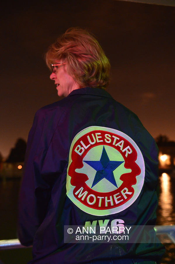 Freeport, New York, USA. September 10, 2014. A Blue Star Mothers of America member looks at the shimmering night lights from houses along the canal while sailing on board the boat Miss Freeport V, which set sail from the Woodcleft Canal of the Freeport Nautical Mile after a dockside remembrance ceremony in honor of victims of the terrorist attacks of September 11 2001, on the eve of the 13th anniversary of the 9/11 attacks. On her jacket is NY6, for the Long Island Blue Star Moms Chapter. Non-political Blue Star Mothers of America gives support for mothers with sons or daughters who are, or were, actively serving in the war.