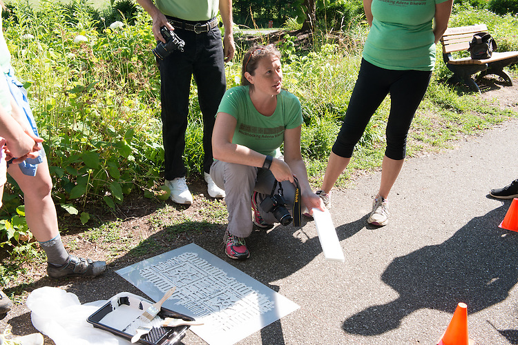 Annie Laurie Cadmus, director of sustainabilty at Ohio University, gives volunteers instructions before painting mile markers on the HockHocking Adena Pathway. ©Ohio University / Photo by Kaitlin Owens