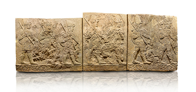 Hittite sculpted orthostats panels of Long Wall Limestone, Karkamıs, (Kargamıs), Carchemish (Karkemish), 900-700 B.C. Soldiers. Anatolian Civilisations Museum, Ankara, Turkey<br /> <br /> Figures of helmeted warriors. They have their shield in their back and their spear in their hand. The prisoner in their front is depicted as small. The lower part of the orthostat is decorated with braiding motifs. <br /> <br /> On a White Background.