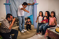 Carlos Saldana takes a photo of Vicky Delgadillo's daughter, Jenny and her grandchildren, Adolfo, Renata, Vicente and Regina as they attend a birthday party and family gathering at the house of Vicky's daughter in Xalapa, Mexico on November 4, 2017. <br /> Photo Daniel Berehulak for The New York Times
