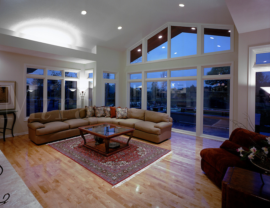 The interior of a contemporary design living room with hardwood floors, modern furniture and large glass windows.
